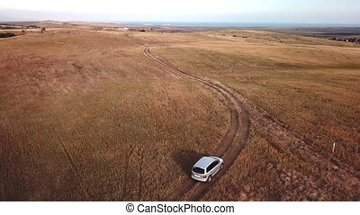 Car driving off road through dry land - Aerial view of a car...