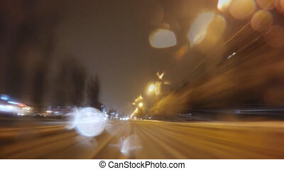 Car driving on a night city road at