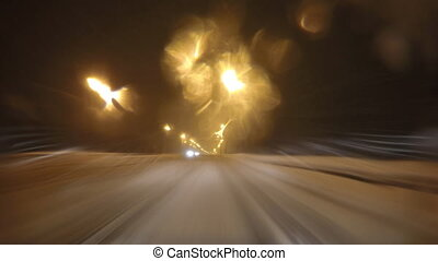 Car driving on a night city road at winter snowfall