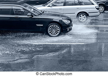 car driving on flooded road with splashing water after heavy rain