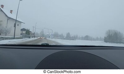 Car driving on snow covered road in winter. Driver s point of view looking through window.