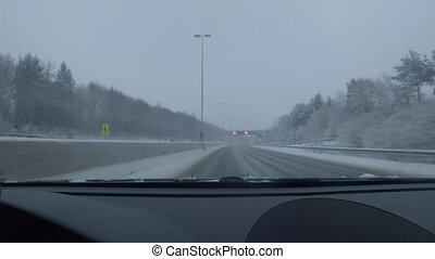 Car driving on snow covered road in winter. Driver's point of view looking through window.
