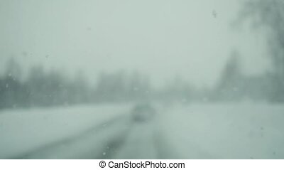 Car driving on snow road during deep snowfall in slowmotion.