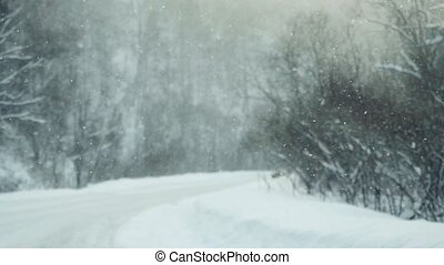 Car driving on snow road during snowfall in slowmotion. 1920x1080