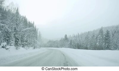 Car driving on snow road during snowfall in slowmotion.