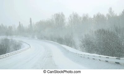 Car driving on snow road during snowfall in slowmotion....