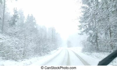 Car driving on snow-covered snowy forest road in winter. Drivers point of view looking through window.