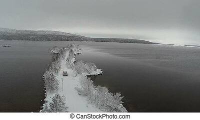 Car driving on winter island road in the river, aerial view