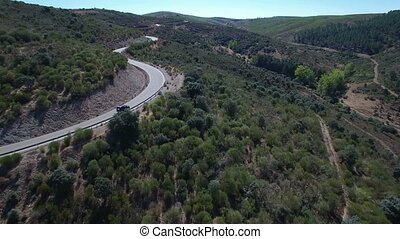 Car driving over curved mountain road - Aerial view of car...