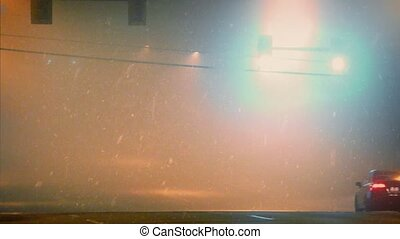 Cinematic view of car driving under traffic lights at night in heavy snowstorm