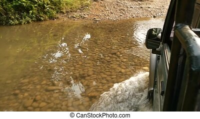 Car driving through shallow creek. View of car crossing...