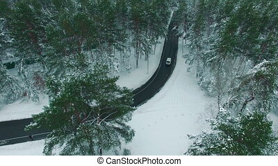 Car driving through snowy pine forest in winter aerial drone footage