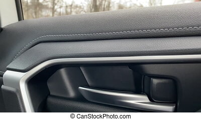Car driving through the city streets car interior door trim panel, handle and lock switch close-up.