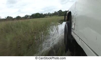 car driving wet fileld land Arfica safari - Africa wild...