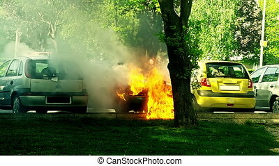 Car engulfed in flames with lot of smoke on the parking lot....