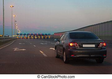 Car entrance on paid road in the evening
