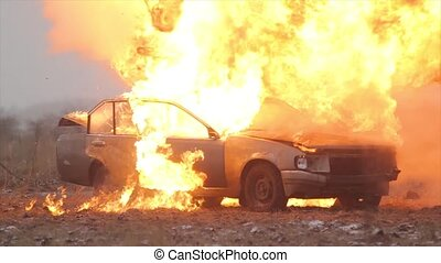 Car Explosion In Slow Motion, Car burns in a gray field -...