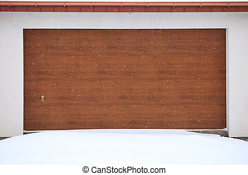 car garage door surrounded by snow