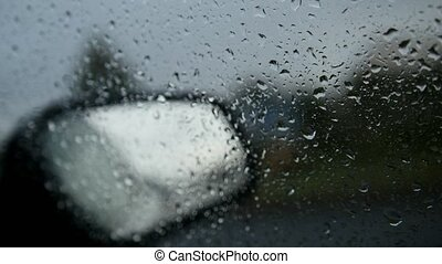 Car glass on a rainy day - defocused background. Moving...