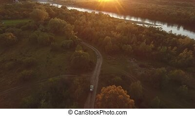 Car Goes in a Field off the Road at Sunset