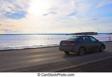 car goes on the road lake in winter
