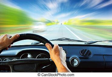 Car - Hands on steering wheel of a car driving on an asphalt...