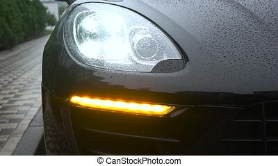 Car headlight flashing in the rain