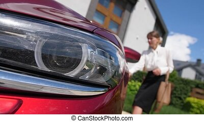 Close-up of car headlight flashing while blurry on background businesswoman unlocking doors pressing button on key fob. Adult female driver in formal clothing unlocking doors of auto parked near house