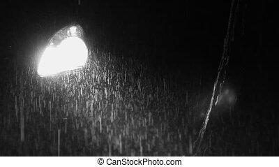 Car headlight on rainy night. B&W.