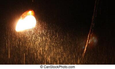 Car headlight on rainy night.