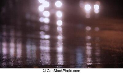 Car headlights and rain on wet pavement at night.