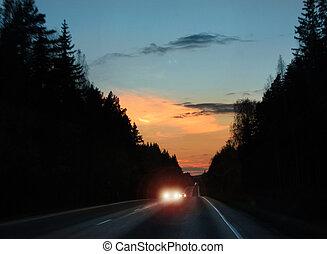 Car headlights glare in evening traffic