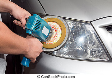 Car headlights with power buffer machine at service station...