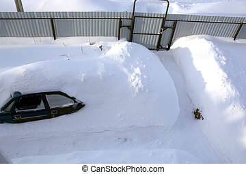 Car in a snowdrift near the house, top view. The passenger car was covered with snow. There is a lot of snow outside.