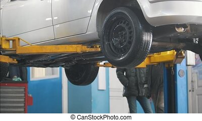 Car in auto service lifting for repairing, mechanics in...
