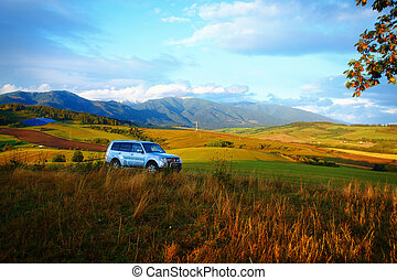 car in landscape with snow mountain and yellow and green meadows. With Solar power plant on background.