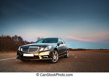 Modern luxury business sedan in the light of evening sun