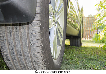 Car in the Parking lot on the grass, rear wheel close-up. Selective focus, outdoor, summer