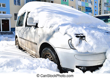 car in the snow against the background of the house on a sunny day, a large snow drift, close-up