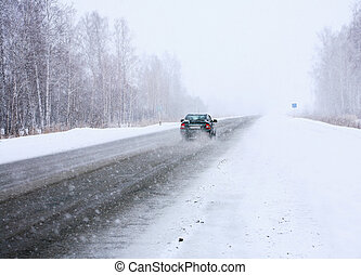 car in winter on way to snowfall and blizzard
