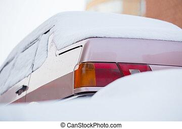 car in winter under snow
