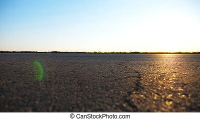 Car is driving on asphalt road at the countryside. Automobile rides along the highway with beautiful landscape at background. View on the country road. Travel concept. Slow motion