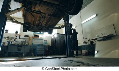 Car is lowered in automobile service for checking, worker repairs detail