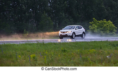 car is moving on a wet road in the rain