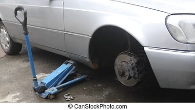 Car is on the jack for wheel replacement - Gray metallic car...