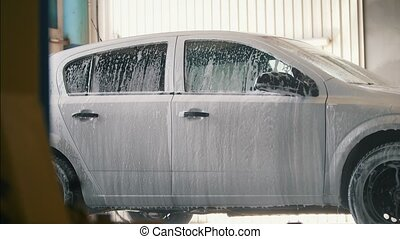 Car is washing with cleaning foam in car-washing facility