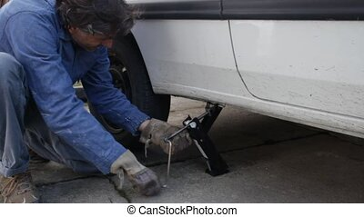 car jack  - Jacking up a car with the emergency jack