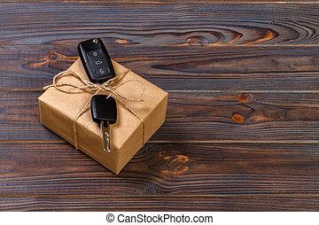 car key and gift box on dark background