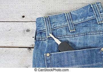 Car key in blue jeans back pocket against wooden background