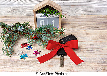 Car key with colorful bow and calendar, christmas tree, branches, snowflakes, on wooden background